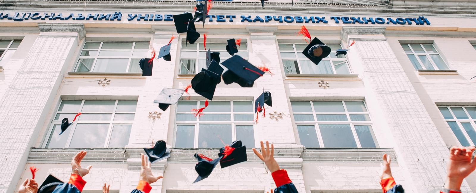 Hands throwing graduation caps in the air.